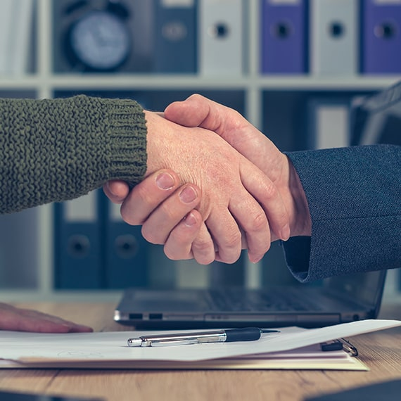 Man and woman shaking hands over business